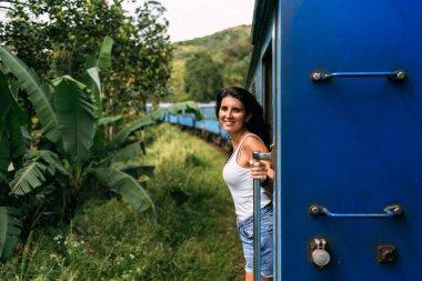 Beautiful girl traveling by train among mountains. The girl travels by train to beautiful places. Travel by train. Travelling to Asia. Trains Sri Lanka. Railway transport. Railway. Transport Asia
