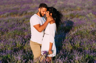 Couple in love on lavender fields. Boy and girl in the flower fields. Honeymoon trip. Honeymoon. Newly married couple. Couple travels. Lavender meadows. Lover. Happy couple. Lovers at sunset