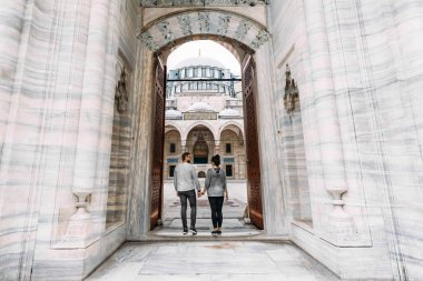 Traveling couple near the mosque. Beautiful mosque in Istanbul. Wedding trip the newlyweds. Tourists in Turkey. Follow me. Boy and girl holding hands. Tourists on the tour. Man and woman in the mosque