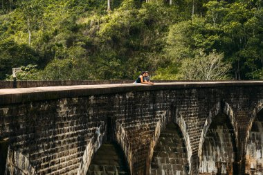Loving couple hugging on the bridge. Guy and girl traveling around Asia. The couple travels to Sri Lanka. Man and woman in an unusual place. Nine-arch bridge. Travellers in Asia. Honeymoon trip