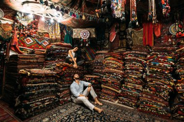 Couple having fun. Couple in love in Turkey. Man and woman in the Eastern country. Gift shop. A couple in love travels. Persian shop. Tourists in store. Oriental carpet. Cappadocia. Morocco
