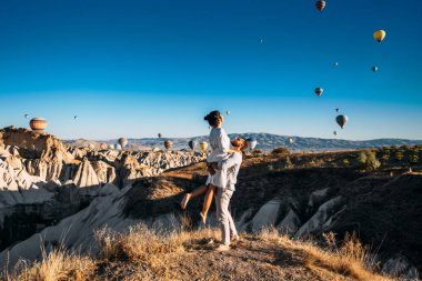 A couple in love in Cappadocia. The couple travels the world. Vacation in Turkey. Honeymoon in Cappadocia. Happy couple traveling. Honeymoon trip. Hot air balloon flights. Woman in the arms of a man