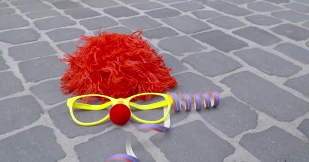 Egy vicces parókát, szemüveget álcázzák, egy orr a hab anyaga és a szerpentin, kövezett talajon - karnevál koncepció vagy ünnep fogalma - Prores