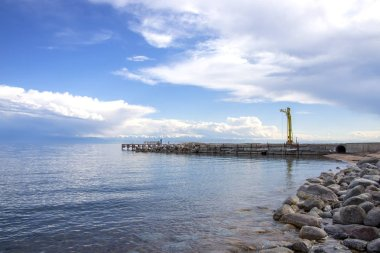 View of Issyk-Kul Lake, a mountain range with snow-capped peaks and a pier from a rocky beach