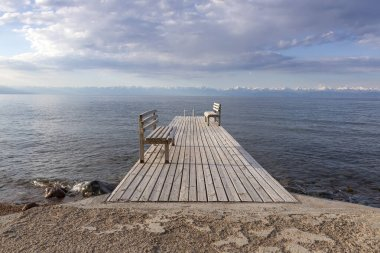 Pier with benches on Lake Issyk-Kul with a mountain range with snow-capped peaks on the horizon and a cloudy sky