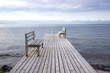 Pier with benches on Lake Issyk-Kul with a mountain range with snow-capped peaks on the horizon