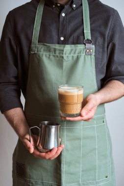 Barista makes coffee. A man holds a milk jug and a glass of coffee. The guy makes cappuccino, pouring whipped milk into espresso. Barista in a kitchen apron. Equipment for professional service