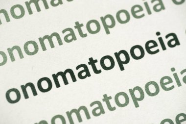 word onomatopoeia printed on white paper macro