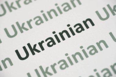 word Ukrainian language printed on white paper macro