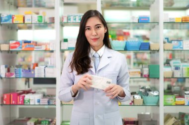 Asian young woman pharmacist with a lovely friendly smile holdin