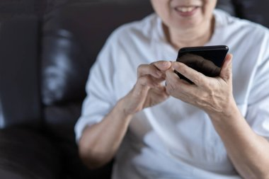 Elderly woman using her phone in home