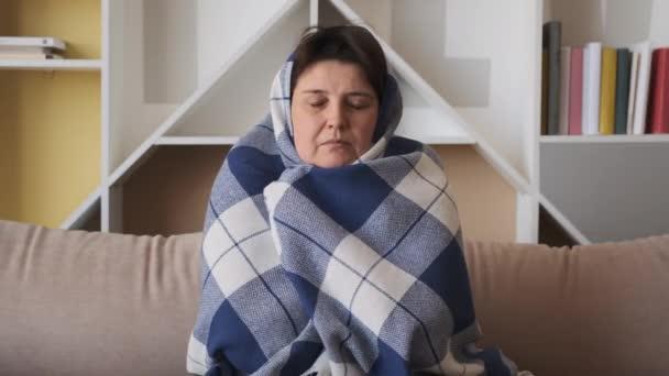 Frau erfriert zu Hause. krankes krankes Mädchen mit Fieber Grippe Temperatur Symptome in Decke gehüllt zittern drinnen.