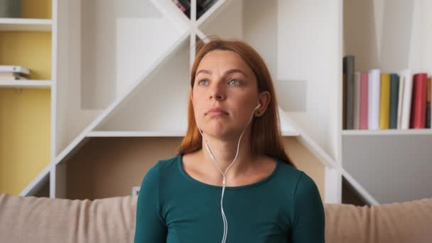 Calm happy young woman in headphones chilling sitting on sofa listening to favorite music. Mood wearing earphones at home