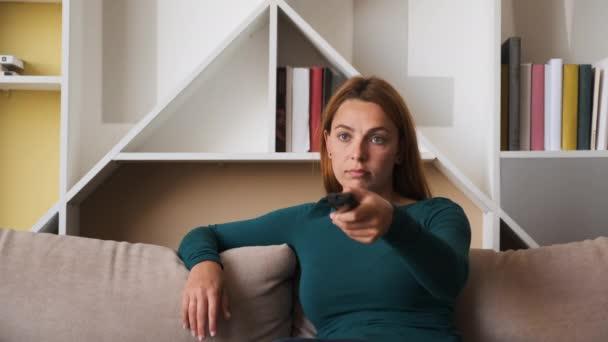 Schöne fröhliche Frau sitzt auf dem Sofa im Wohnzimmer und wechselt die Kanäle mit einer Fernbedienung, während sie fernsieht