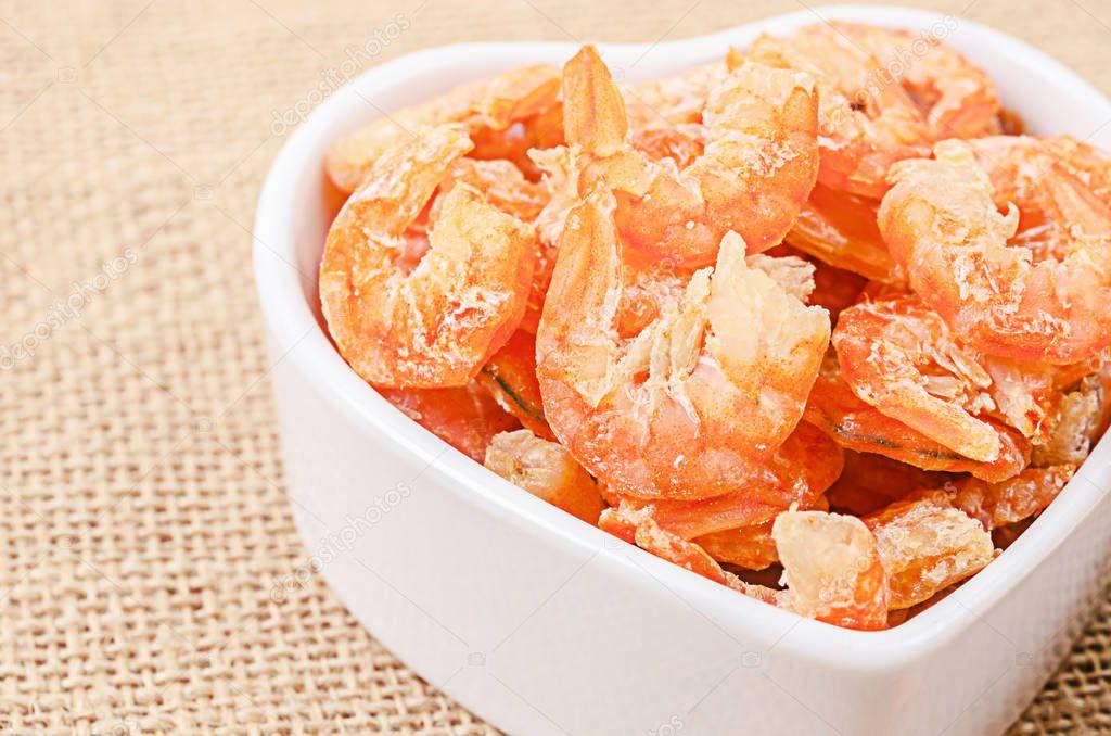 Dried shrimp in white bowl on sack background.