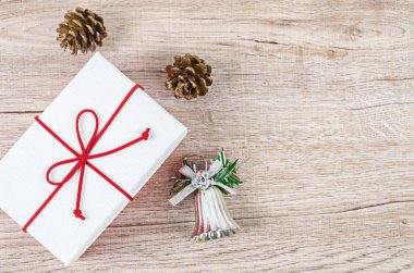 White present with red ribbon and christmas decoration.