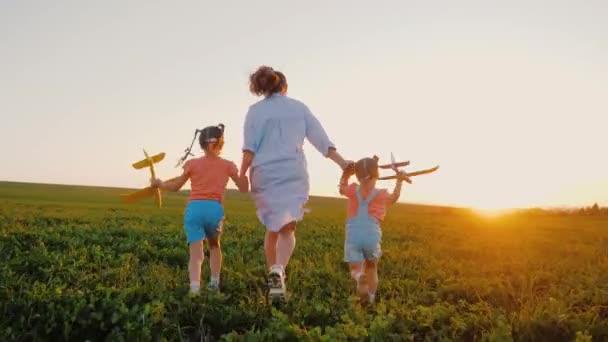 Matka běží ruku v ruce s dcerami v poli, děti hrají hračky letadla