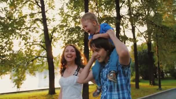 Šťastní rodiče drží roztomilé dítě v náručí, objímají a baví