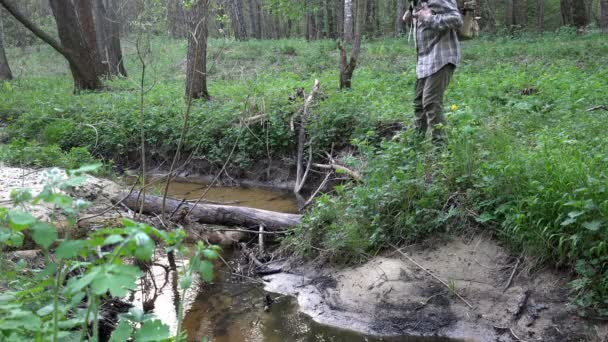 Cestovatel s batohem opatrně prochází lesní potok podél padlý strom Sochorová