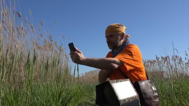 Ekologicky šetrné prostředky, zralý muž mluví o mobilní telefon a má sluneční, uprostřed Reed poblíž řeky