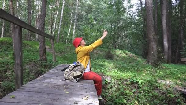 Zralá žena cestující sedí na mostě přes léto potoku a bere obrázky a rozhovory prostřednictvím video volání na telefonu