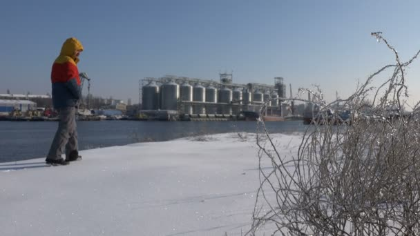 Male worker is walking along bank of a winter river on background of an industrial view of granaries in port