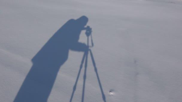 Stín muže novinář ve sněhu. Kameraman s kamerou a stativem
