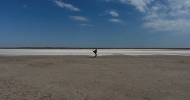 Mature female traveler with a backpack walks on muddy oily bottom of salty white lake under scorching midday sun