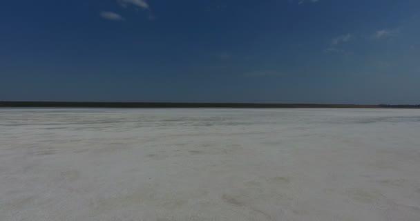 Aerial view of a white salt lake, white landscape to horizon. Birds seagulls flying on the horizon