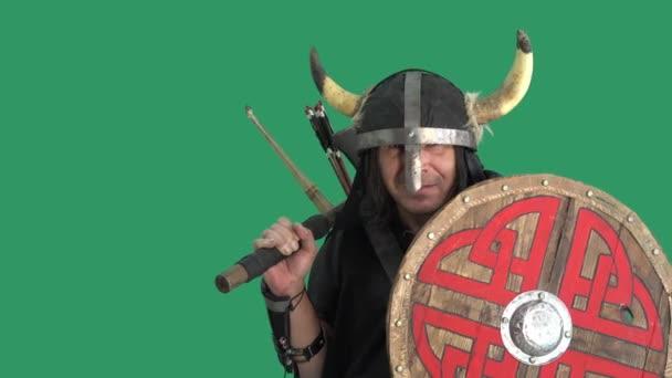 Portrét muže ve vikingském kostýmu se štítem a v helmě s rohy. Výhružně se dívá do dálky zpod ocelové přilby. Zelené pozadí