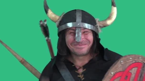 Šílený Viking v helmě s rohy, se štítem a velkou sekerou s veselým vzhledem tance a úsměvy. Portrét muže - zelené pozadí