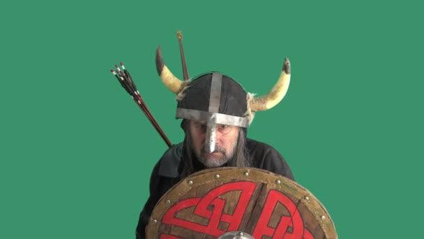 Portrét agresivního rozzlobeného staršího Vikinga v helmě s rohy, vyhrožujícího sekerou a křičícího nadávky. Muž na zeleném pozadí