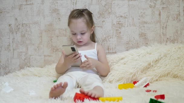 Kid plays on the phone while sitting on the couch with the designer. Toy in the smartphone. Life as a distance preschool education. Modern baby