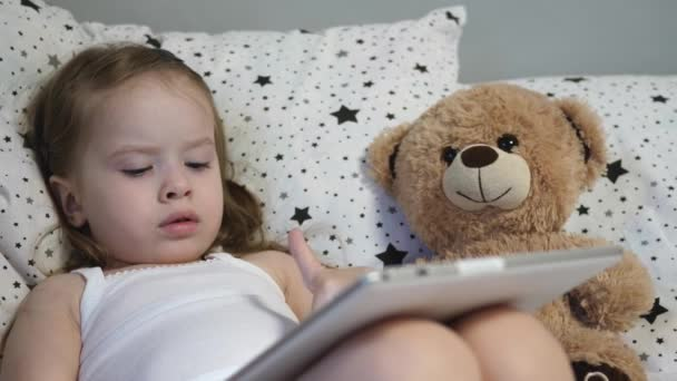 Little happy child plays a tablet while lying on a bed with a teddy bear. The kid watches the childrens channel through the touch monitor. Teaching a preschooler remotely online. Close-up