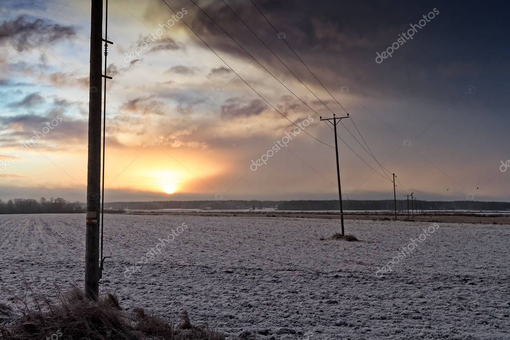 The telephone lines lead through the frosty fields of the rural Finland on a cold winter morning. The birds are trying to find food over the frozen fields.