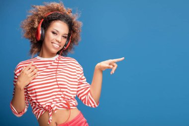 Adorable african american woman with red headphones smiling, looking at camera, blue background.