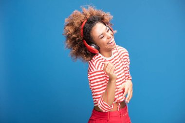 Adorable african american woman with red headphones laughing out loud, blue background.