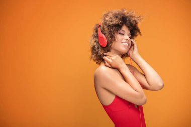 Adorable african american woman with red headphones listening to music, yellow background.