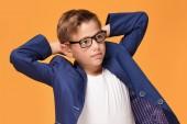 Elegáns kisfiú pózol a háttér narancssárga stúdió, divatos szemüveg és kabátot visel.