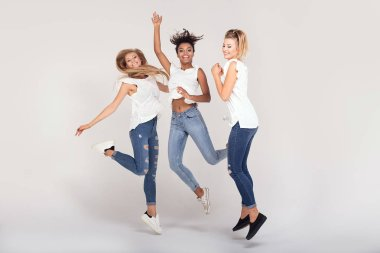 Group of young multi-ethnic attractive girls wearing white shirts, smiling and having fun together, posing in studio.