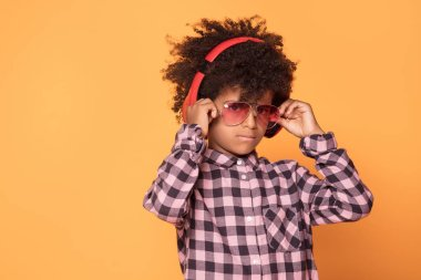 African american little man in fashionable shirt. Studio shot. Young boy posing on yellow background.