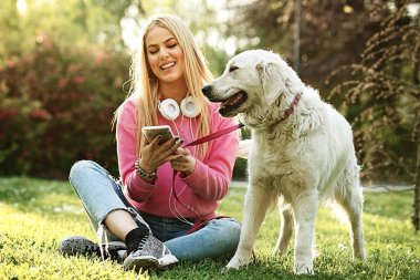 Young blonde woman is relaxing in the park with her retriever.