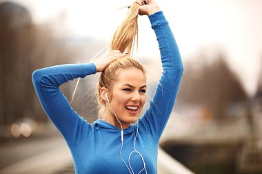 Young woman is enjoying after exercise on the bridge and listening music.