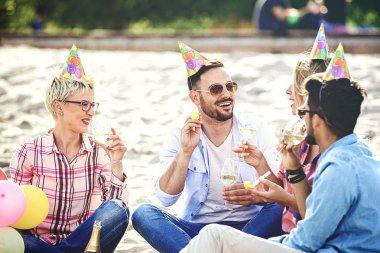 Friends enjoying birthday party on the beach.