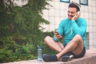 Man is listening music and relaxing after jogging.