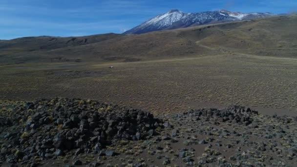 Štěrková cesta s a přípojného vozidla. Tromen sopka na pozadí. Národní park. Wylde osamělá krajina. Letecká drone scéně jde vpřed procházející blízko podlahy s kameny. Neuquen, Patagonie