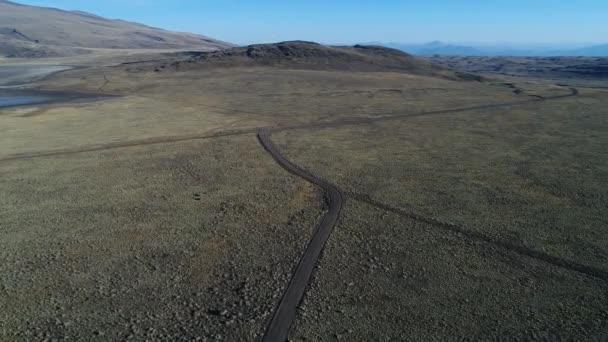 Letecká drone scéně prázdné silnice štěrk. Kamerou pohybující se vpřed. Estepa tromen národní park, chos malal, neuquen, patagonia argentina