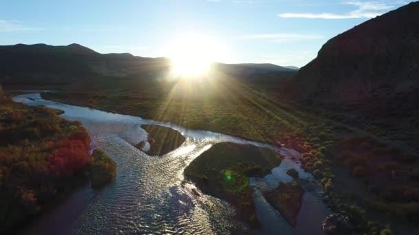 Letecká DRONY. Barrancas řeky na západ slunce, zlaté hodiny, podsvícení. Rozděluje stát Neuquen - Mendoza, Argentina. Kamera pohybuje dopředu a dolů. Podzimní barvy na stromech. Hmyz, procházející blízko fotoaparátu
