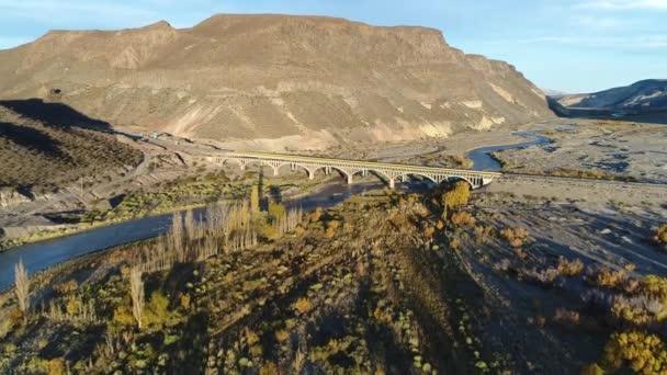 Letecká drone scéně barrancas řeky na západ slunce, zlaté hodiny. Řeka, dělení Neuquen z Mendoza, Argentina. Fotoaparát, přesun dopředu, přes vintage mostní konstrukce na pozadí. Auto procházet