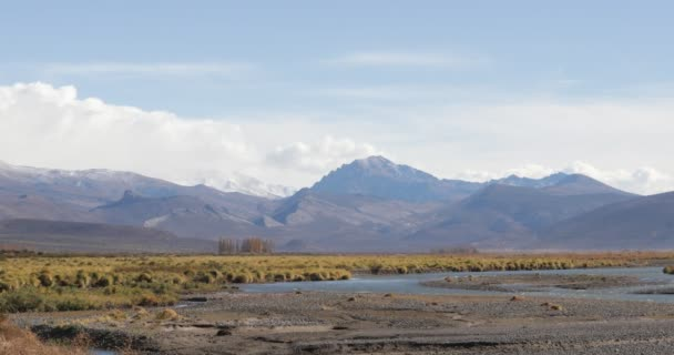 Mendoza grassland and steppe landscape with Rio Grande river thaw river and andes mountains on the background. Patagonia and cuyo, Argentina.